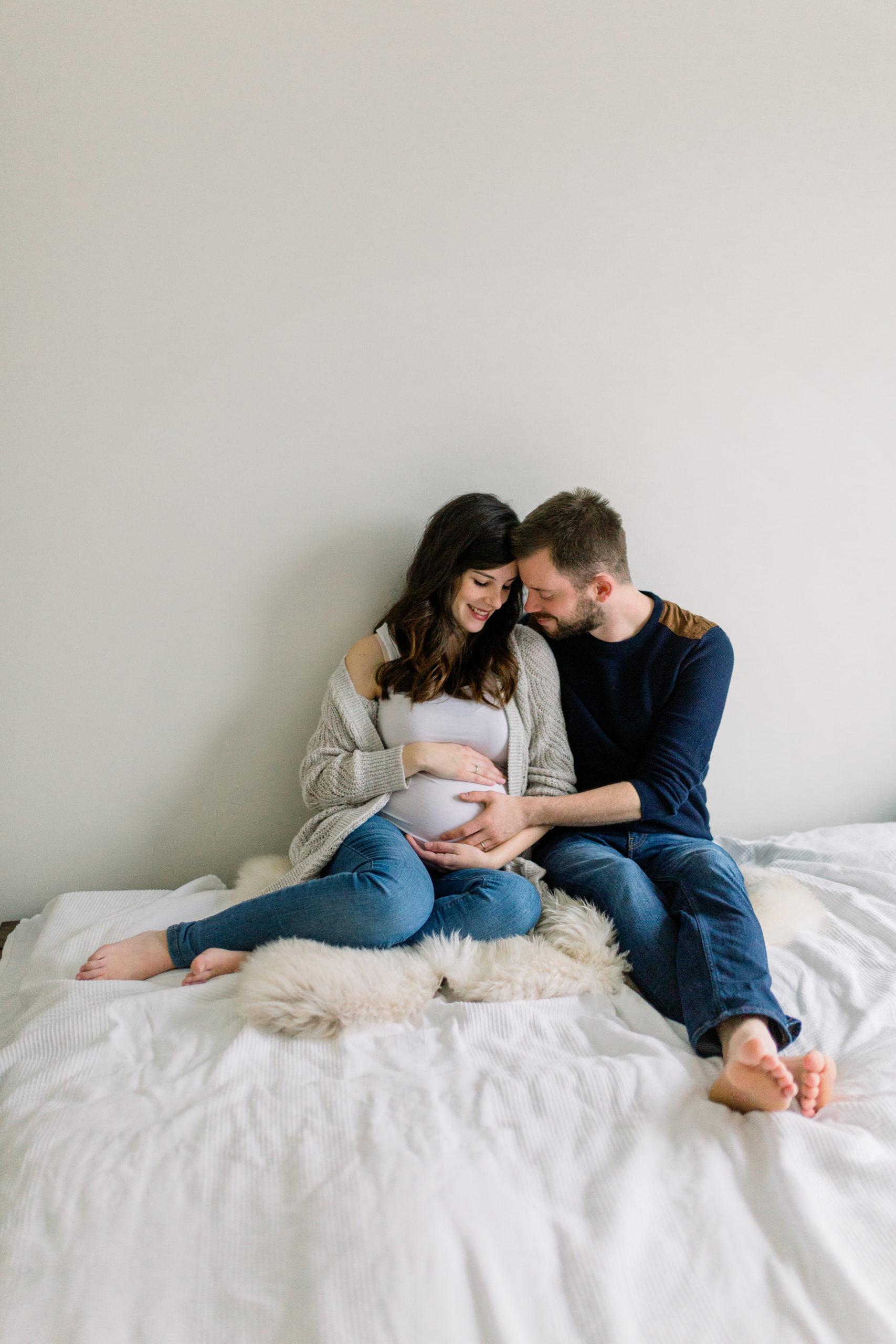 Babybauch mit Partner. Sitzen auf dem Bett